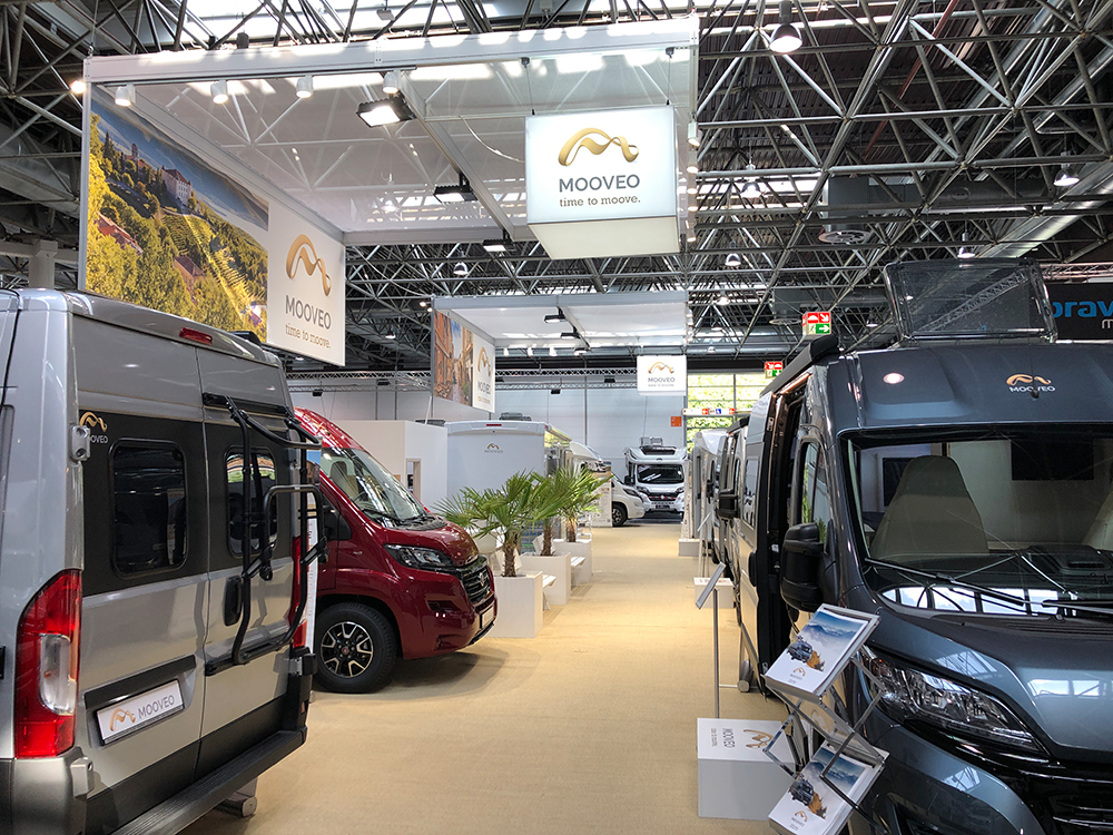 Fahrzeuge für Camping stehen in einer Messehalle