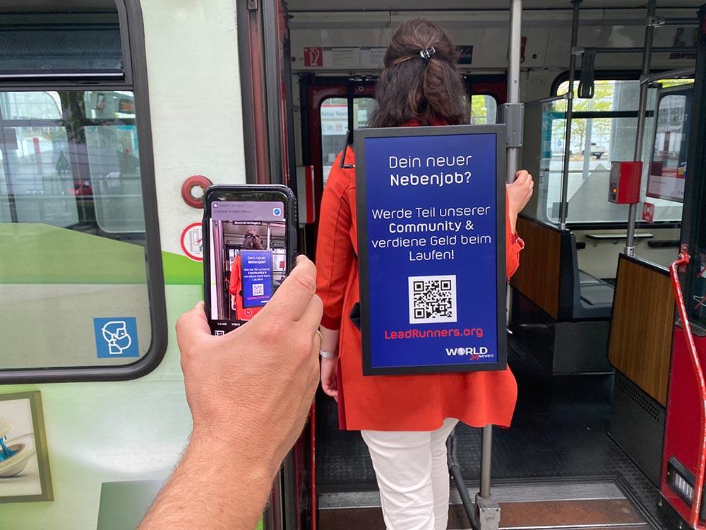 Frau trägt einen Monitor Rucksack und steigt in Straßenbahn als Nebenjob